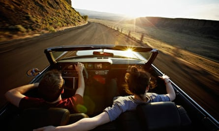 young couple driving sunset