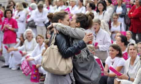 Two women kiss in front of people taking part in a demonstration against gay marriage