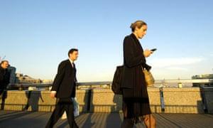Office workers walk across London bridge