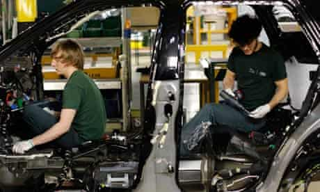 Two workers inside the body shell of a Range Rover Evoque SUV