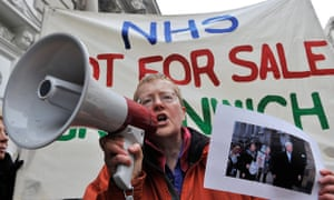 Man with megaphone in front of banner reading 'NHS not for sale'