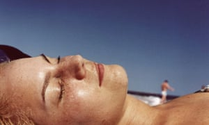 Young woman sunbathing on beach, close-up, side view
