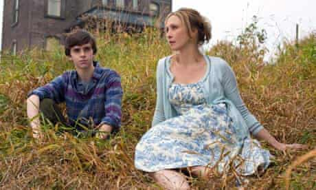 Vera Farmiga as Norma and Freddie Highmore as Norman Bates sitting on grass outside house