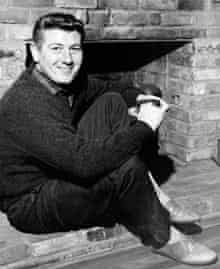 Jack Clement sitting by a fireplace