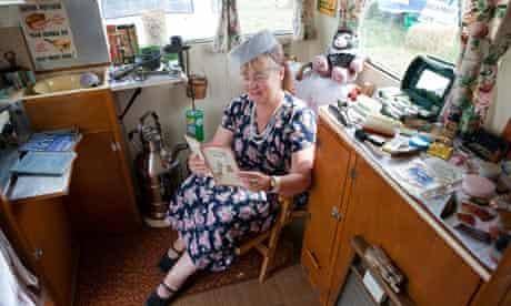 Karen Poole sitting in her caravan museum surrounded by 1940s paraphernalia