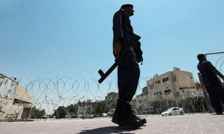 A police officer watches as razor wire is installed on the outskirts of Manama, Bahrain