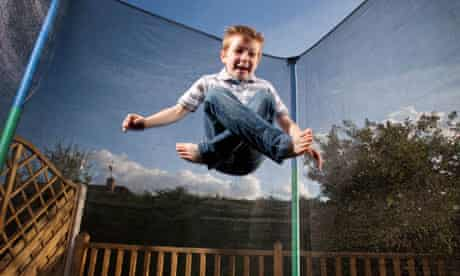 Young boy playing on a garden trampoline with a safety net around the edge