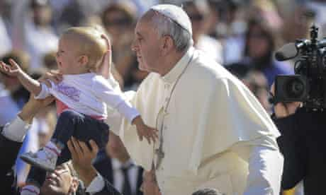 The pope blesses a child in St Peter's Square, Vatican City.