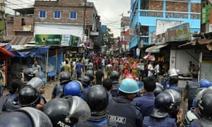Bangladeshi police block the road in front of protesting garments workers