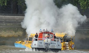 A fire brigade rescue team approchaes the London Duck Tours vehicle that caught fire.