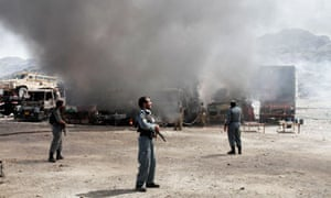 Afghan police officers watch the site of a militant attack at Torkham, near the Pakistan border.