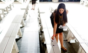 A worker puts down programs on benches before a presentation of the Honor Spring/Summer 2014