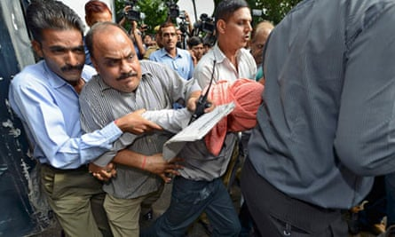 Plainclothes policemen escort an Indian teenager to a juvenile court in New Delhi
