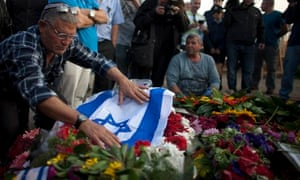 People pay their respects next to the grave of Ariel Sharon