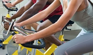 Men and women cycling on exercise bikes