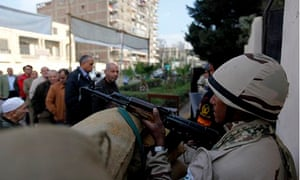 A soldier with a rifle outside a polling station in Cairo, with people queuing in the background