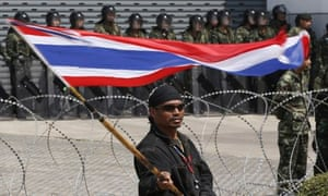 An anti-government protester waves a Thai flag as he stands in front of army soldiers.