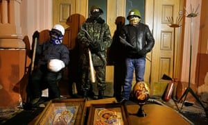 Helmeted protesters armed with improvised weapons at the entrance to justice ministry