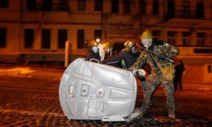 Anti-government protesters use a rubbish container to build a barricade