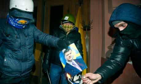 Protesters burn a photo of President Viktor Yanukovych