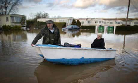 Man and woman in a boat amid flooded caravans