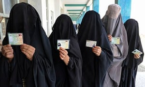 Burqa-clad women show ID cards as they wait to vote in Afghanistan's 2009 presidential elections