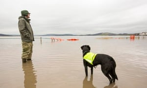A man walks road through coastal floodwaters in Storth, Cumbria