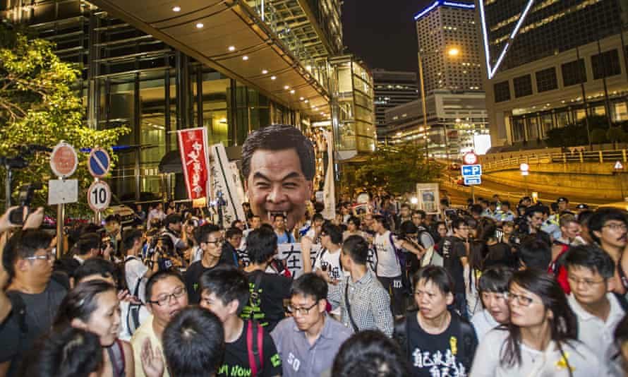Public enemy No 1 … pro-democracy protestors march towards Government House in Hong Kong, holding a