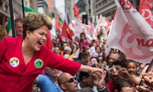 Dilma Rousseff, smiling, shakes a supporter's hand at a crowded rally