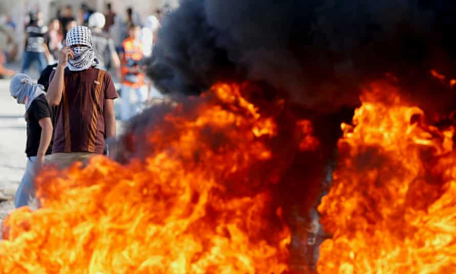 Palestinian protester stands near burning tyres during clashes with Israeli police in East Jerusalem