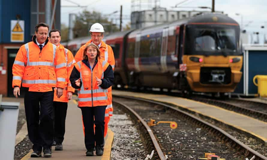 George Osborne and David Cameron in high-vis jackets with train in background