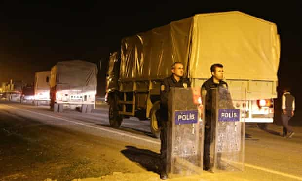 Turkish security forces stand guard as the peshmerga convoy arrives in Suruç, just north of the Turk