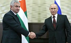 Abkhazia's President Raul Khadzhimba and Vladimir Putin shake hands