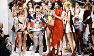 Crowd of models around John Galliano on catwalk