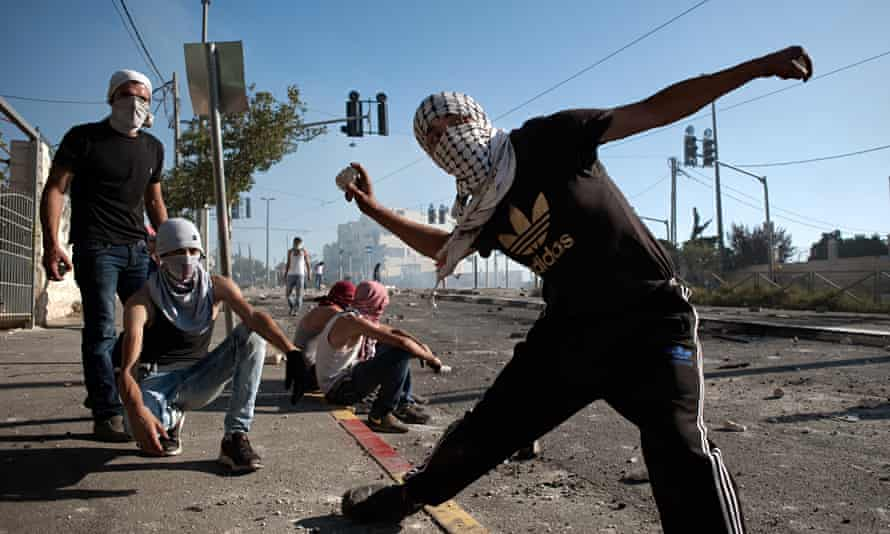 A Palestinian boy hurls stones to Israeli police during clashes in Shu'afat