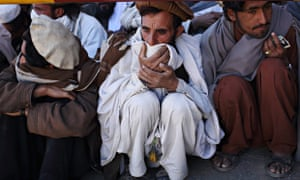 Refugees at the Gulan camp in Khost province, Afghanistan, crouching on ground