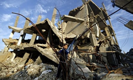 A Palestinian boy plays in the rubble of a house destroyed during clashes between Israel and Hamas