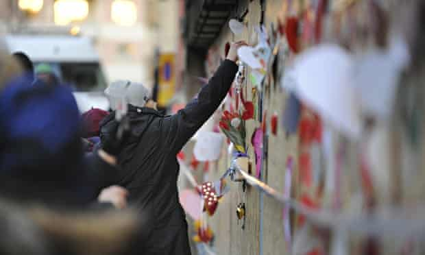 People place flowers and cards outside a mosque after a fire in Eskilstuna, Sweden