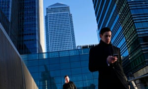 A worker looks at his phone at the Canary Wharf business district in London