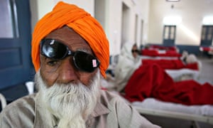 A patient awaits treatment at a hospital after undergoing cataract removals in India