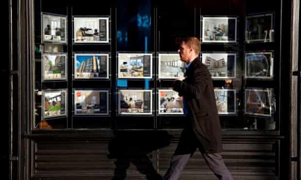 Man walking past an estate agent's window