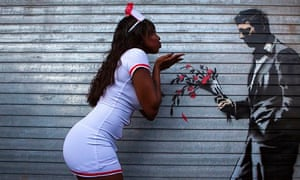 A dancer poses playfully with a Banksy graffito of a man offering flowers on a wall in New York