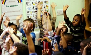Children with their hands in the air at a nursey