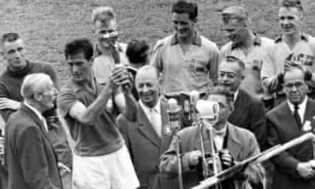 Bellini lifts the 1958 World Cup trophy with officials and Swedish players in the background
