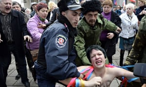 A police officer and pro-Russian demonstrators tussle with a topless Femen activist outside the Crim