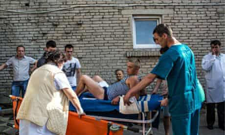 Ukrainian soldier wounded in the checkpoint attack is transferred to an ambulance in Volno