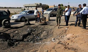 Army personnel look at hole in the ground at site of checkpoint explosion near Benghazi, Libya