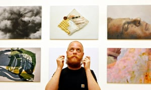 Man standing in front of photographs of art