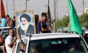 Volunteer Iragi fighters in Baghdad carry a portrait of Ayatollah Ali al-Sistani.