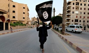 A member loyal to the Islamic State in Iraq and the Levant (ISIS) waves an ISIS flag in Raqqa